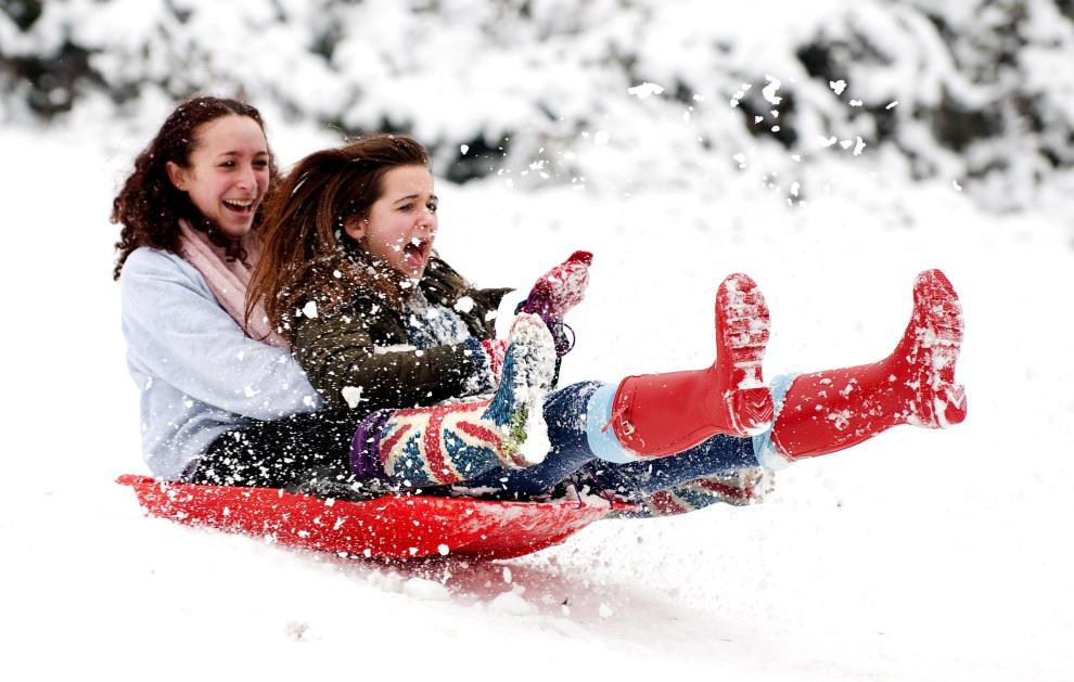 13.WIELKA BRYTANIA, Londyn, 5 lutego 2012: Dziewczyny zjeżdżają z górki w Alexandra Park. AFP PHOTO / LEON NEAL