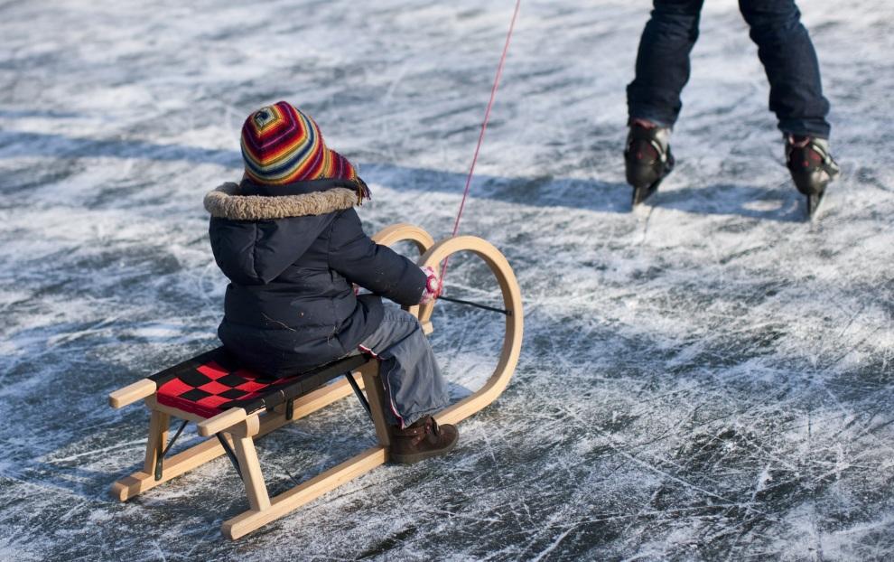 15.NIEMCY, Kolonia, 5 lutego 2012: Dziecko na sankach na zamarzniętym stawie w Kolonii. AFP PHOTO / ROLF VENNENBERND