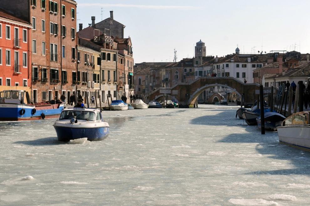 17.WŁOCHY, Wenecja, 6 lutego 2012: Łódka przebija się przez zamarznięte wody kanału. AFP PHOTO / Marco Sabadin