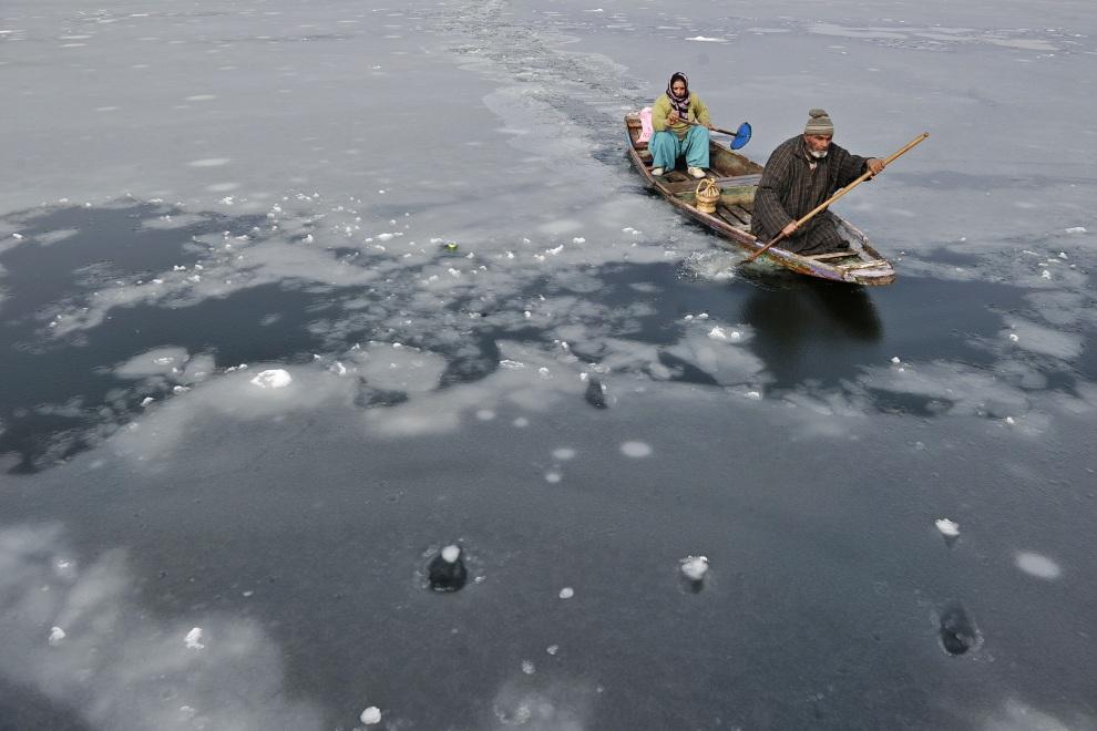 19.INDIE, Srinagar, 17 stycznia 2012: Mężczyzna kruszy lód wiosłem na jeziorze Dal. AFP PHOTO/Tauseef MUSTAFA