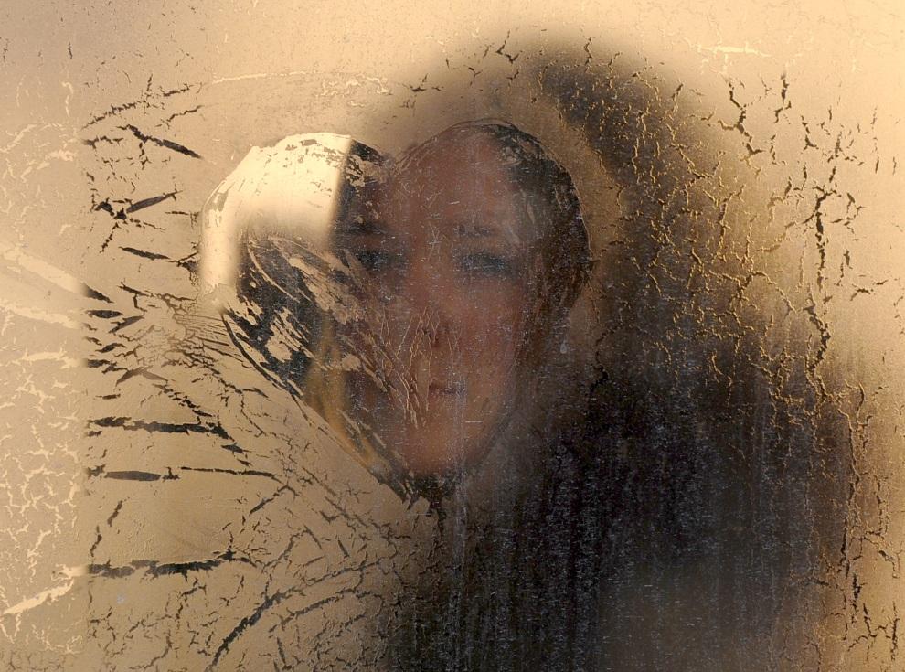 9.BIAŁORUŚ, Mińsk, 2 lutego 2012: Kobieta patrzy przez zamarznięte okno autobusu miejskiego. AFP PHOTO / VICTOR DRACHEV