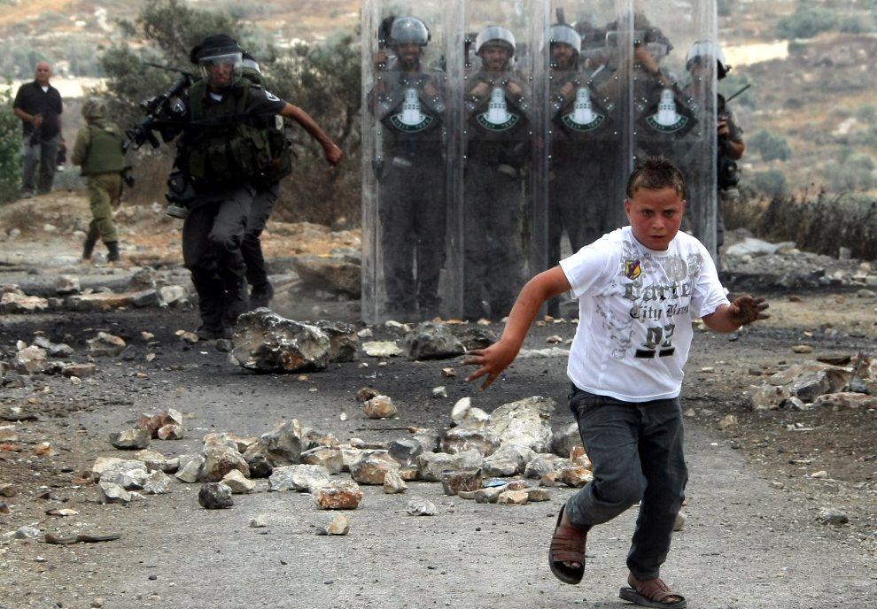 14.ZACHODNI BRZEG, Kafr Qaddum, 22 czerwca 2012: Młody Palestyńczyk ucieka w trakcie starć z izraelskimi żołnierzami. AFP PHOTO/JAAFAR ASHTIYEH