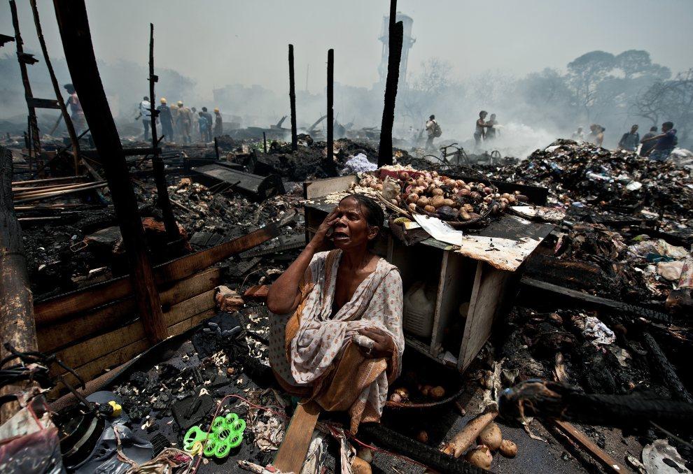 18.INDIE, New Delhi, 22 czerwca 2012: Kobieta rozpaczająca nad dobytkiem strawionym przez pożar w slumsach. AFP PHOTO/ MANAN VATSYAYANA