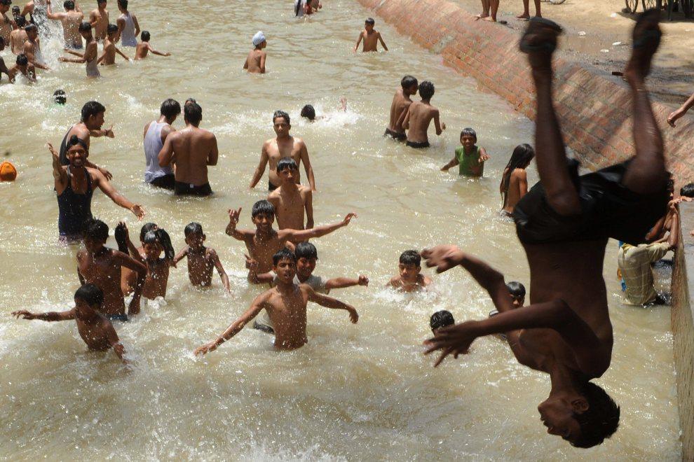 20.INDIE, Amritsar, 17 czerwca 2012: Chłopcy podczas zabawy w kanale wodnym. AFP PHOTO/ NARINDER NANU