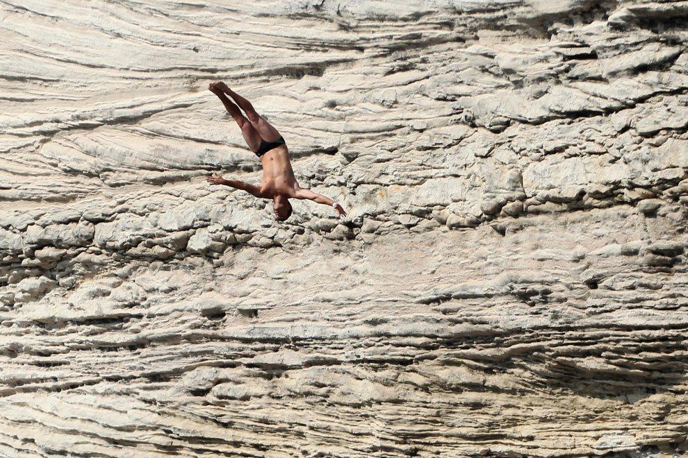 21.FRANCJA, Bonifacio, 21 czerwca 2012:  Steven Lobue skacze z klifu podczas zawodów rozgrywanych na Korsyce. AFP PHOTO / PASCAL POCHARD-CASABIANCA