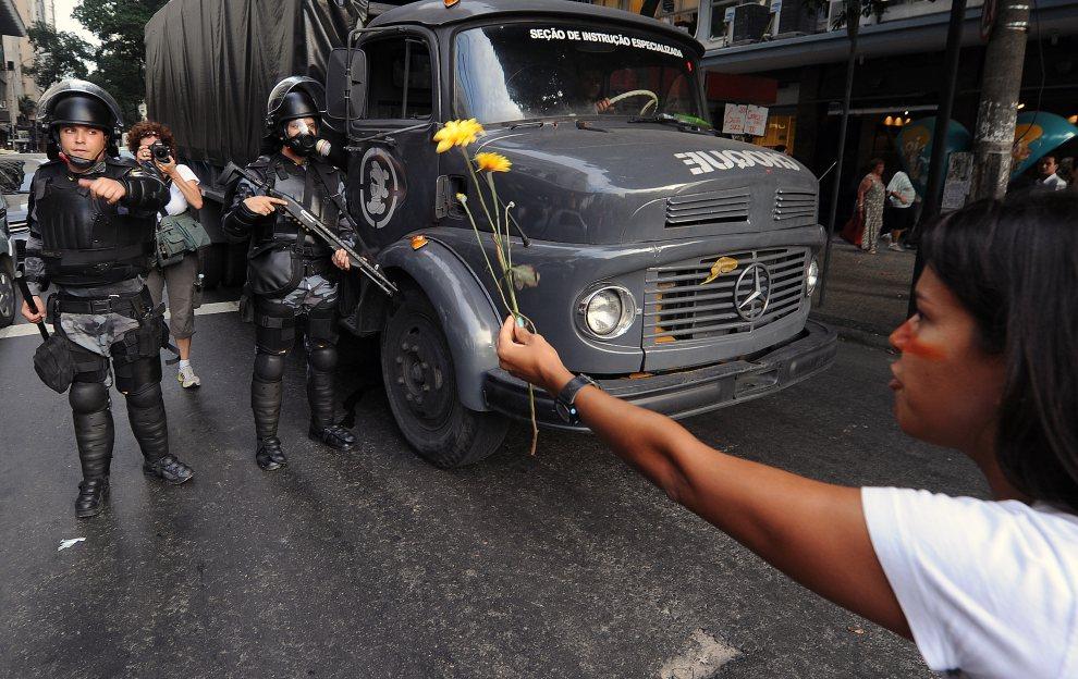 28.BRAZYLIA, Rio de Janeiro, 20 czerwca 2012: Kobieta stara się podać kwiaty policjantom pilnującym porządku podczas jednej z demonstracji. AFP PHOTO / ANTONIO   SCORZA