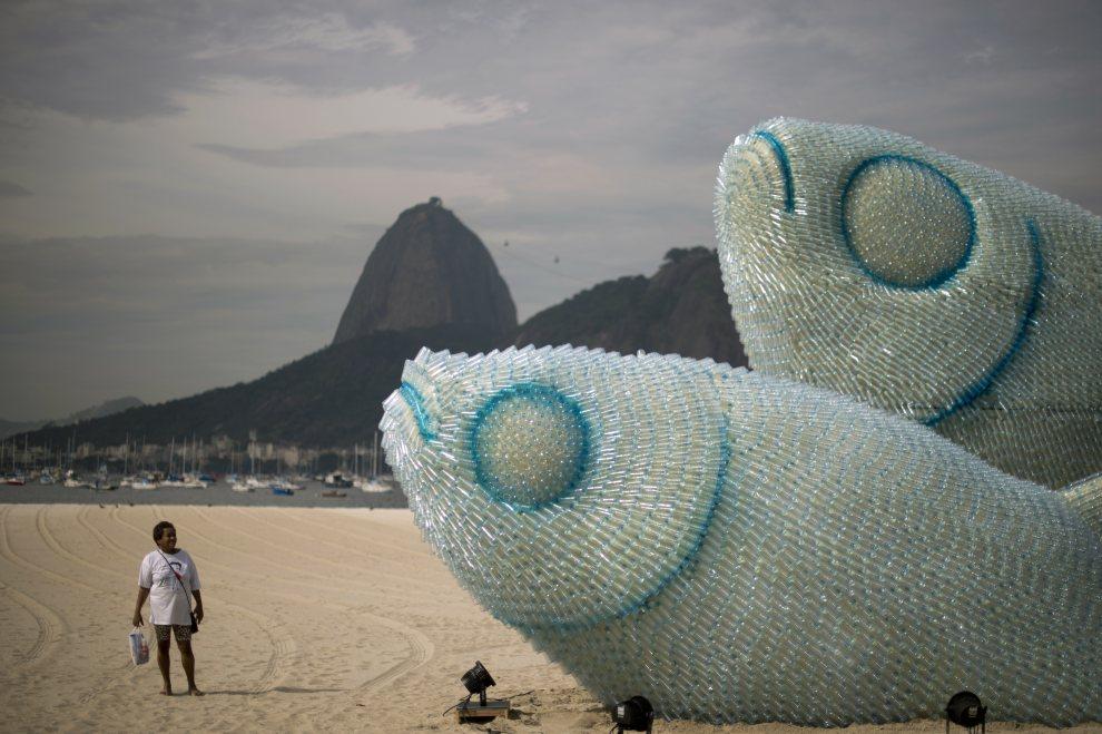 4.BRAZYLIA, Rio de Janeiro, 19 czerwca 2012: Kobieta przygląda się instalacji zbudowanej na plaży z przetworzonych butelek. AFP PHOTO / Christophe Simon