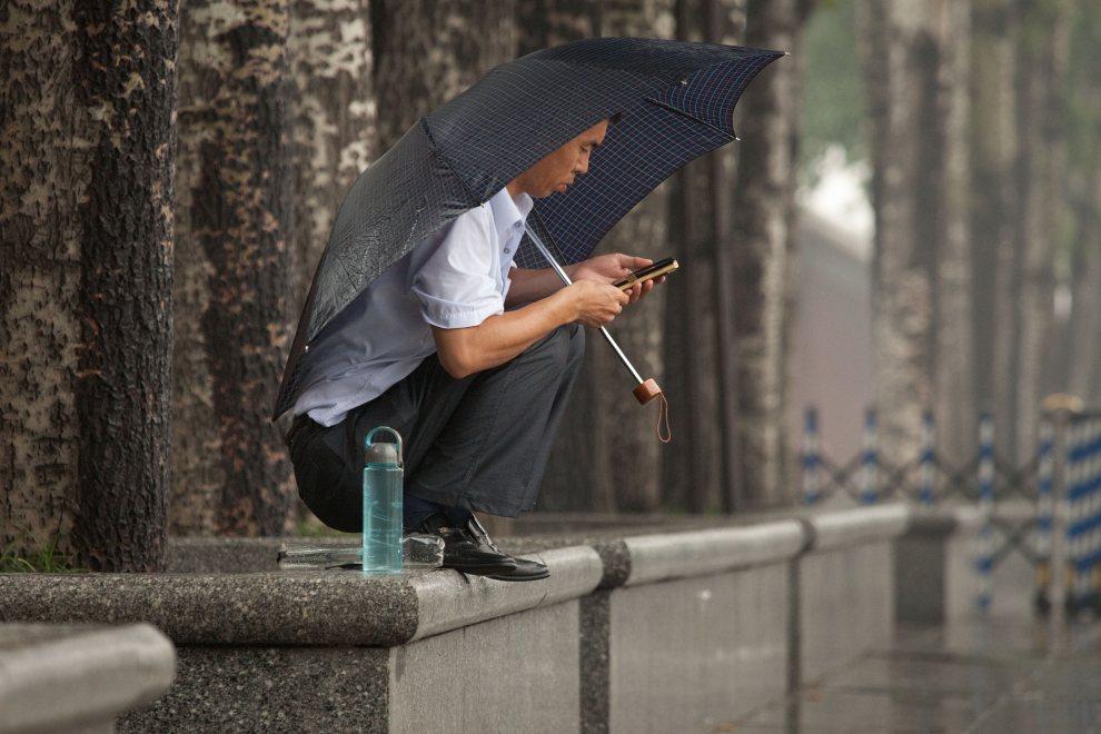 5.CHINY, Pekin, 26 czerwca 2012: Mężczyzna chroni się przed ulewnym deszczem. AFP PHOTO / Ed Jones