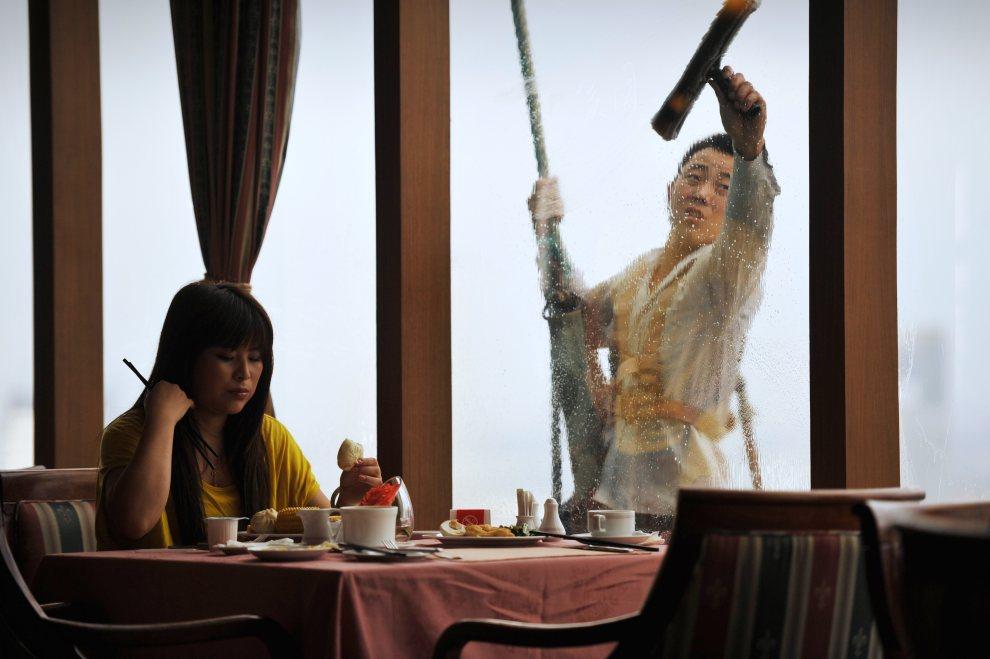 6.CHINY, Ningbo, 21 czerwca 2012: Kobieta jedząca śniadanie i pracownik myjący okna znajdującej się na 23 piętrze restauracji. AFP PHOTO/Peter PARKS