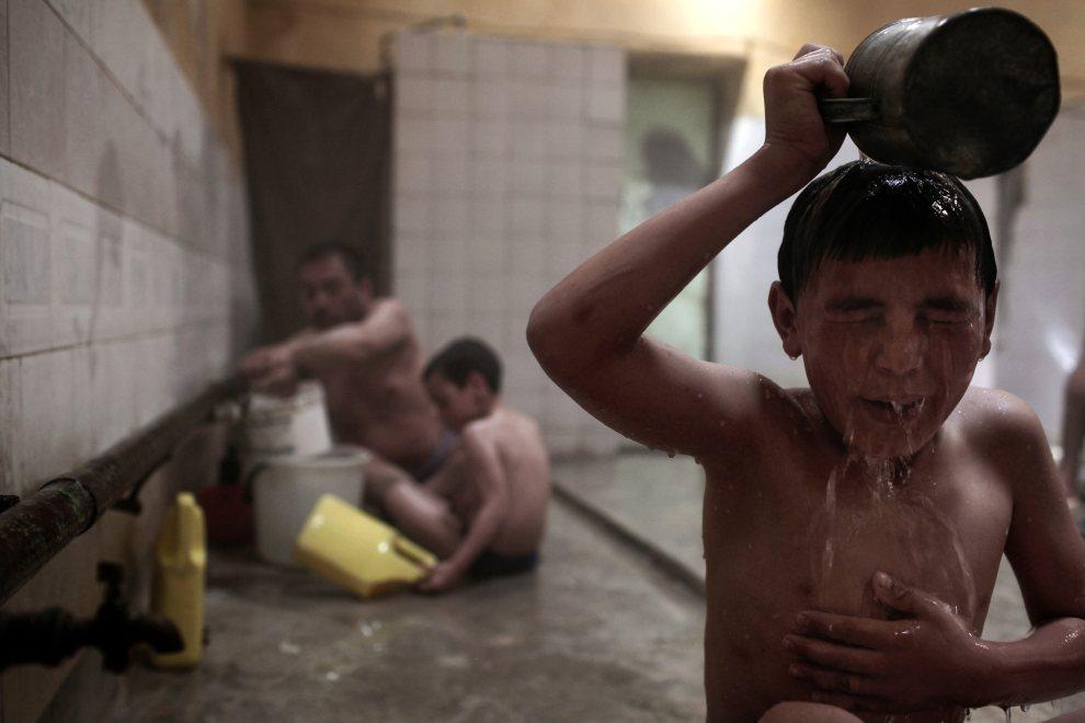 8.AFGANISTAN, Kabul, 30 kwietnia 2010: Chłopiec opłukuje ciało po kąpieli w łaźni. AFP PHOTO/Mauricio LIMA