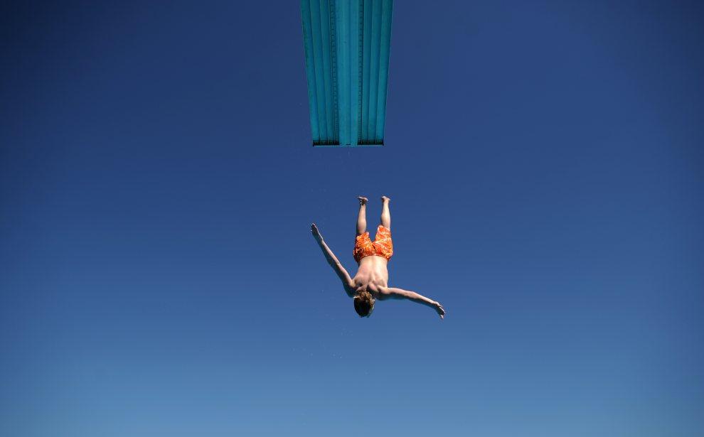 10.NIEMCY, Hanower, 24 lipca 2012: Chłopak skacze do wody podczas odpoczynku na miejskim basenie. AFP PHOTO / JULIAN STRATENSCHULTE