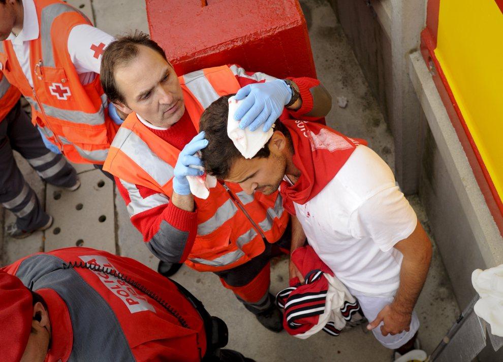 10.HISZPANIA, Pampeluna, 7 lipca 2012: Opatrywanie rany na głowie jednego z uczestników zabawy. AFP PHOTO / PEDRO ARMESTRE