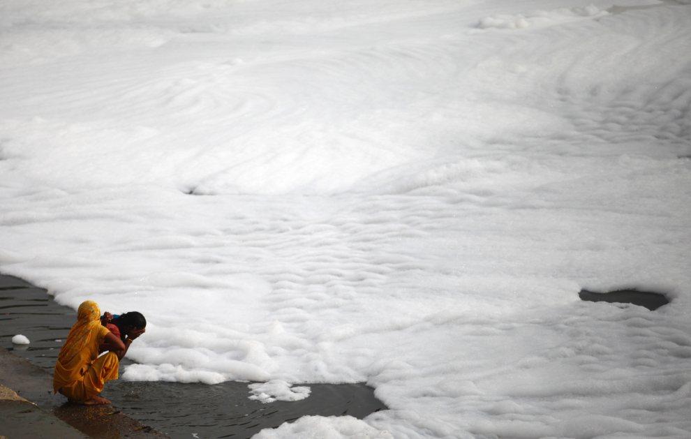 11.INDIE, New Delhi, 14 lipca 2012: Kobieta kąpię się w zanieczyszczonej wodzie. AFP PHOTO/Andrew Caballero-Reynolds