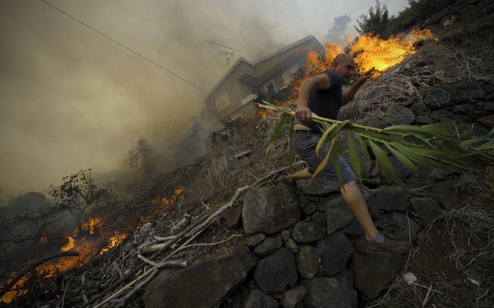 11.PORTUGALIA, Assomada, 21 lipca 2012: Mężczyzna ucieka przed ogniem wdzierającym się między zabudowania. AFP PHOTO / MIGUEL RIOPA