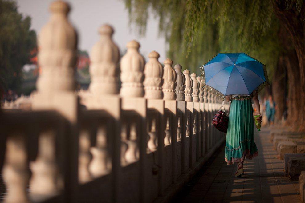 12.CHINY, Pekin, 1 lipca 2012: Kobieta z parasolką na ulicy w Pekinie. AFP PHOTO / Ed Jones