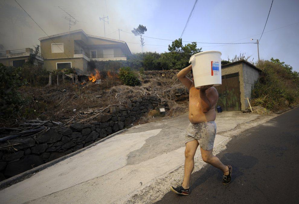 12.PORTUGALIA, Santa Cruz, 21 lipca 2012: Mężczyzna z wiadrem wody pomaga w gaszeniu ognia. AFP PHOTO / MIGUEL RIOPA