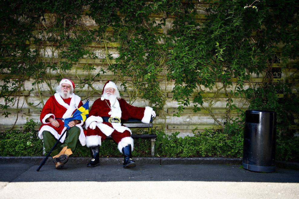 12.DANIA, Kopenhaga, 24 lipca 2012: Mężczyźni przebrani za Mikołajów (uczestnicy kongresu dla Mikołajów) odpoczywają na ławce.  AFP PHOTO / SCANPIX DENMARK / TORKIL ADSERSEN