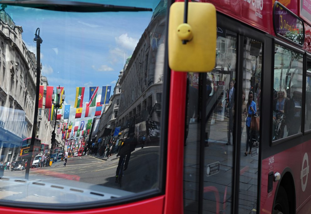 13.WIELKA BRYTANIA, Londyn, 12 lipca 2012: Przystrojona flagami ulica odbija się szybie autobusu. AFP PHOTO / CARL COURT