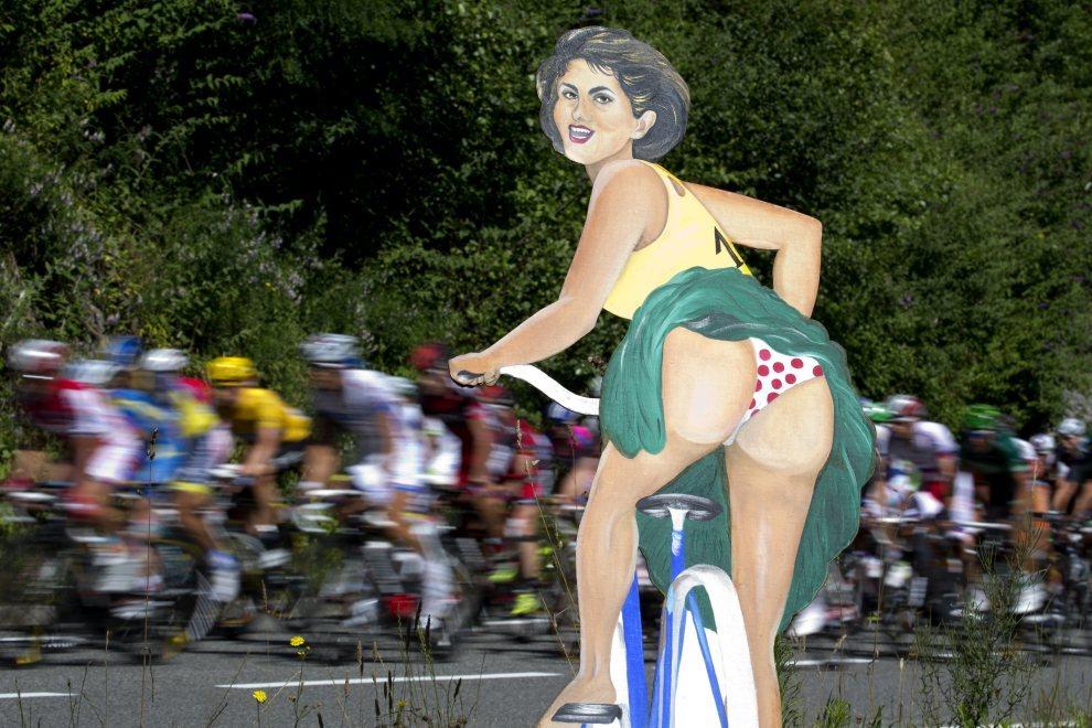 13.FRANCJA, Bagneres-de-Luchon, 18 lipca 2012: Peleton mija podobiznę kobiety na rowerze w bieliźnie w kolorach lidera klasyfikacji górskiej. AFP PHOTO / JOEL   SAGET