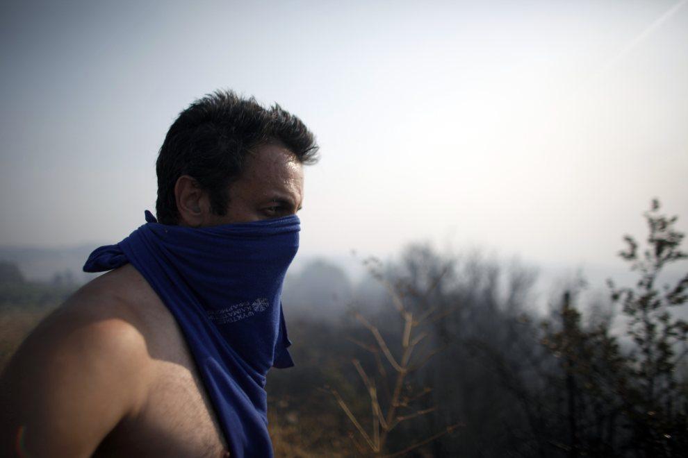 13.GRECJA, Patras, 18 lipca 2012: Mężczyzna przygląda się płonącym lasom w okolicach Patras. AFP / Angelos Tzortzinis