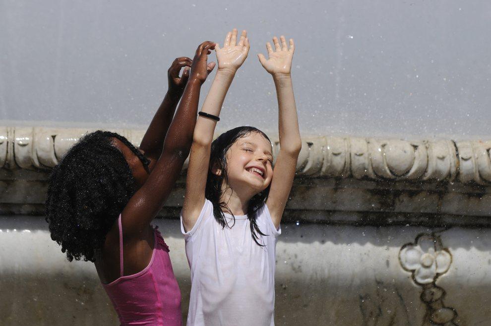 14.HISZPANIA, Sewilla, 24 czerwca 2012: Dzieci bawią się w fontannie podczas upalnego (40 °C w słońcu) dnia. AFP PHOTO / CRISTINA QUICLER