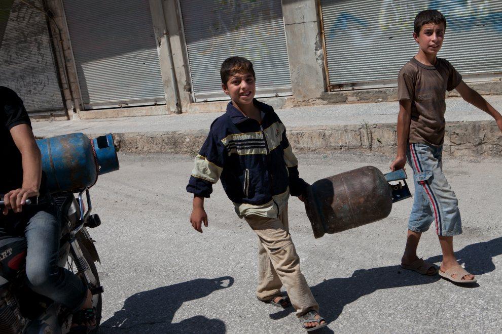 14.SYRIA, in Kfar Nubul, 12 lipca 2012: Chłopcy niosący do nabicia butlę z gazem. AFP PHOTO/LO