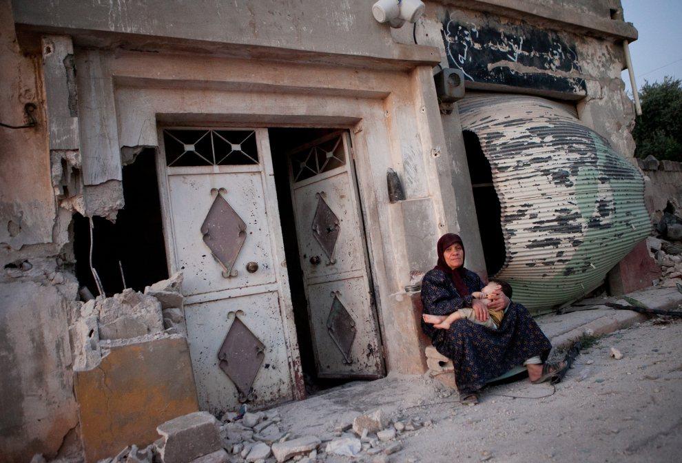 15.SYRIA, Treimsa, 23 lipca 2012: Syryjka z wnukiem przed wejściem do zniszczonego domu. AFP PHOTO/D. LEAL OLIVAS