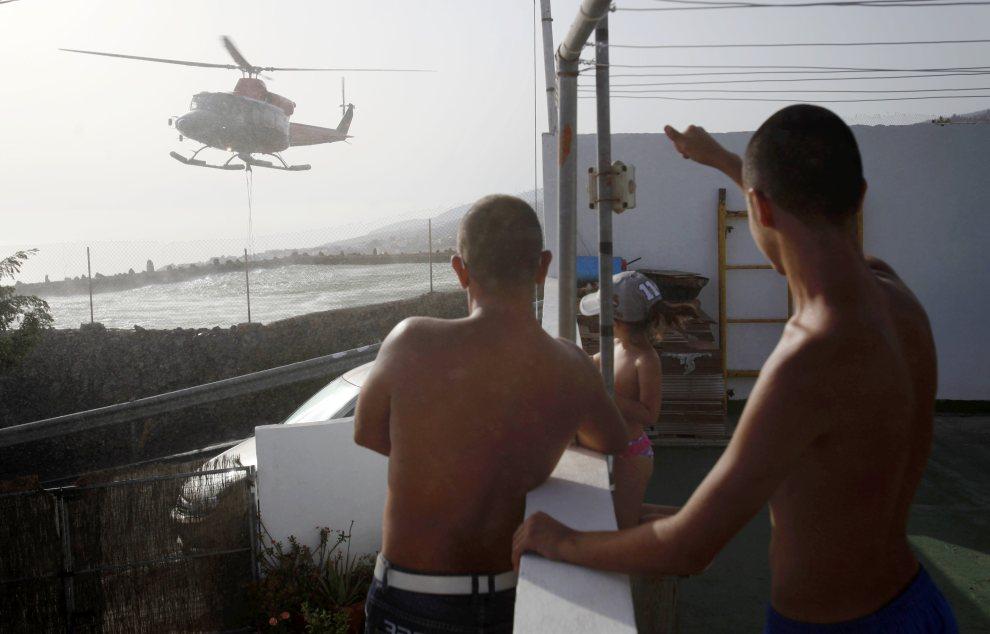 15.HISZPANIA, Teneryfa, 19 lipca 2012: Helikopter nabiera wodę z basenu przy jednym z domów na Teneryfie. AFP PHOTO/Desiree Martin