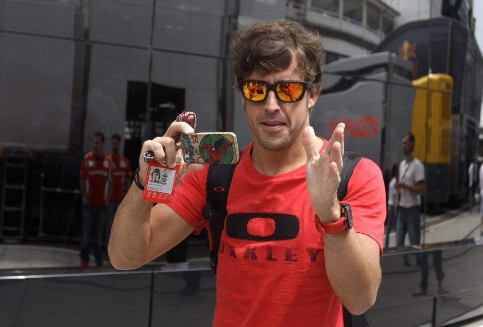 16.WĘGRY, Budapeszt, 26 lipca 2012: Kierowca F1, Fernando Alonso, ustawia fotoreporterów do zdjęcia. AFP PHOTO / PETER KOHALMI