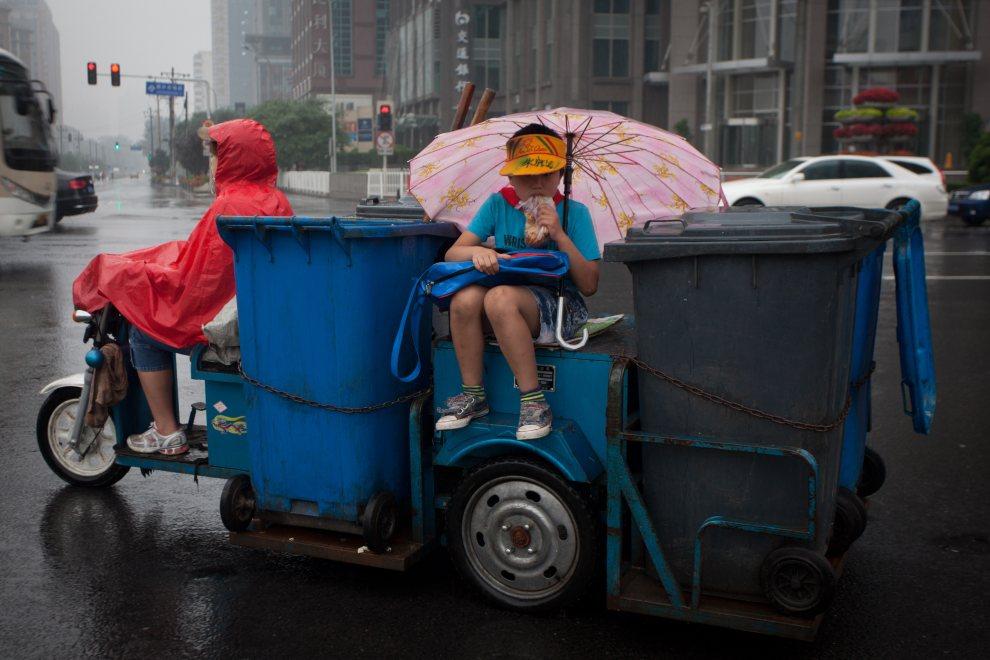 16.CHINY, Pekin, 29 czerwca 2012: Chłopiec z kanapką pomiędzy pojemnikami na śmieci. AFP PHOTO / Ed Jones