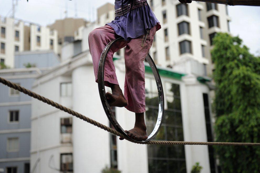 17.INDIE, Ahmedabad, 24 lipca 2012: Chłopiec podczas występu ekwilibrystycznego. AFP PHOTO / Sam PANTHAKY