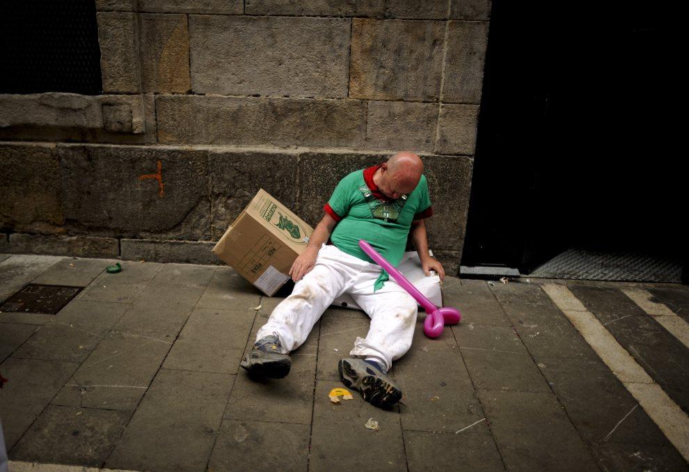18.HISZPANIA, Pampeluna, 10 lipca 2012: Pijany mężczyzna śpiący na ulicy Estafeta. AFP PHOTO/Pedro ARMESTRE