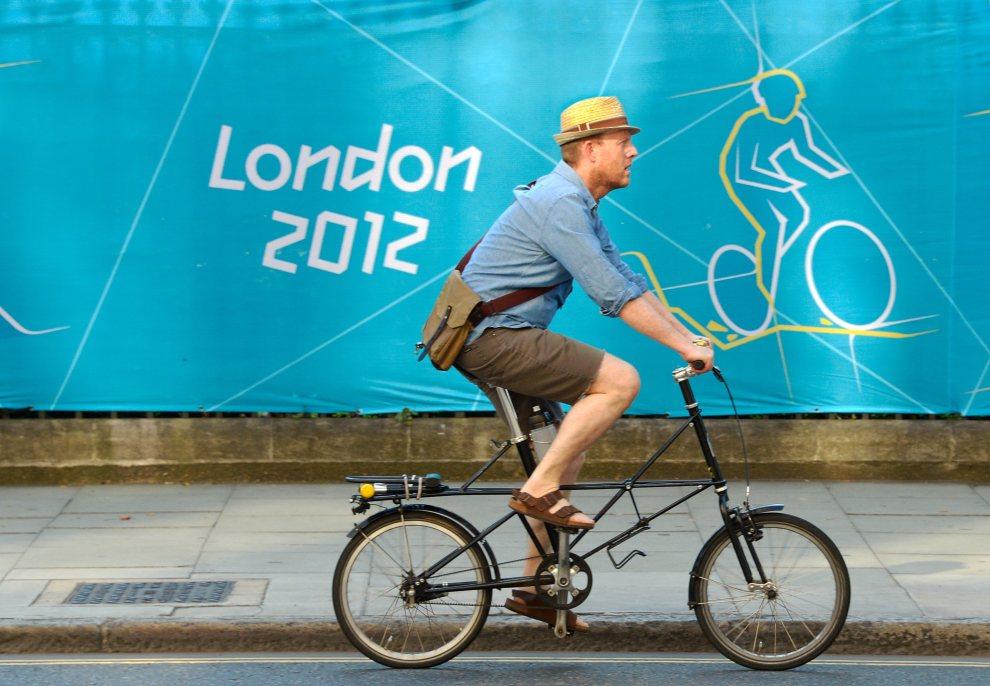 18.WIELKA BRYTANIA, Londyn, 26 lipca 2012: Mężczyzna na rowerze mija banner informujący o występach kolarzy podczas olimpiady. AFP PHOTO / DANIEL GARCIA