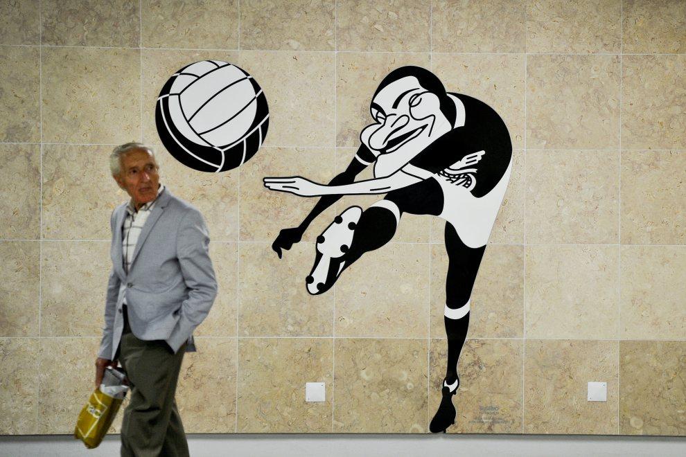 19.PORTUGALIA, Lizbona, 17 lipca 2012: Mężczyzna mija karykaturę przedstawiającą Eusebio. AFP PHOTO/PATRICIA DE MELO MOREIRA