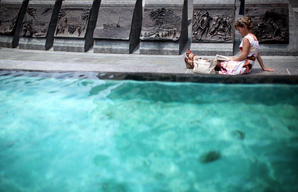 1.USA, Waszyngton, 22 czerwca 2012: Turystka, Lisa Tignor, czyta książkę przy fontannie w pobliżu  pomnika U.S. Navy Memorial. (Foto: Alex Wong/Getty Images)