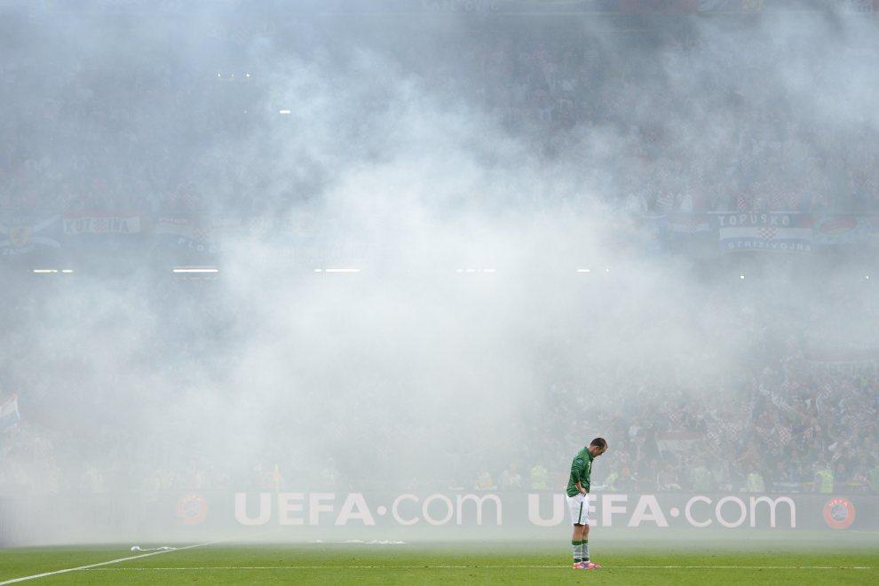 21.POLSKA, Poznań, 10 czerwca 2012: Aiden McGeady (Irlandia) w chmurze dymu z odpalonych rac. AFP PHOTO / FABRICE COFFRINI