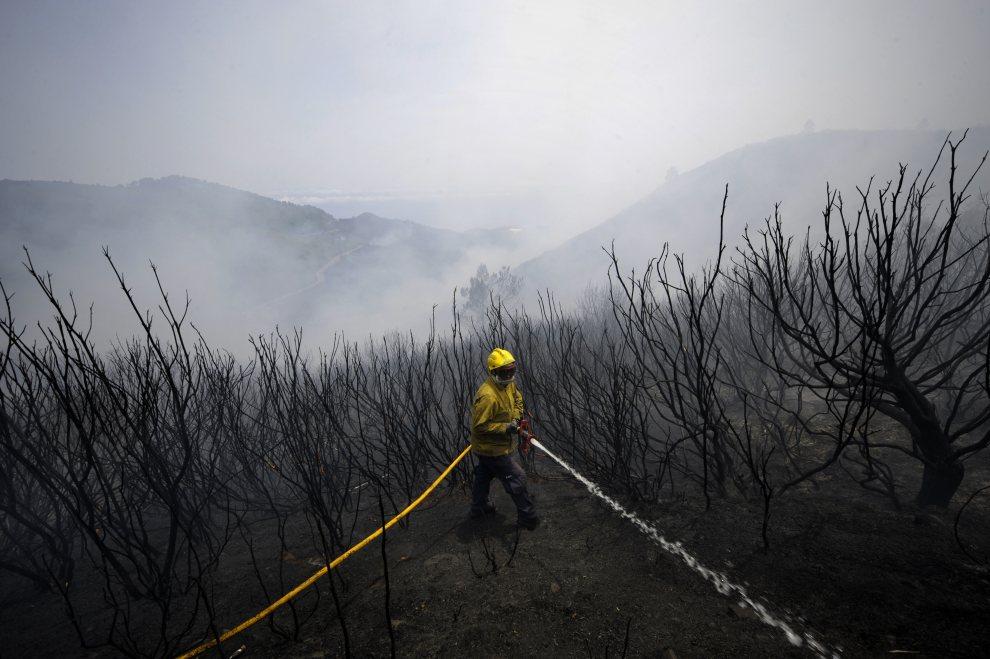 21.PORTUGALIA, Meia Serra, 21 lipca 2012: Strażak dogasza zgliszcza spalonego lasu. AFP PHOTO / MIGUEL RIOPA