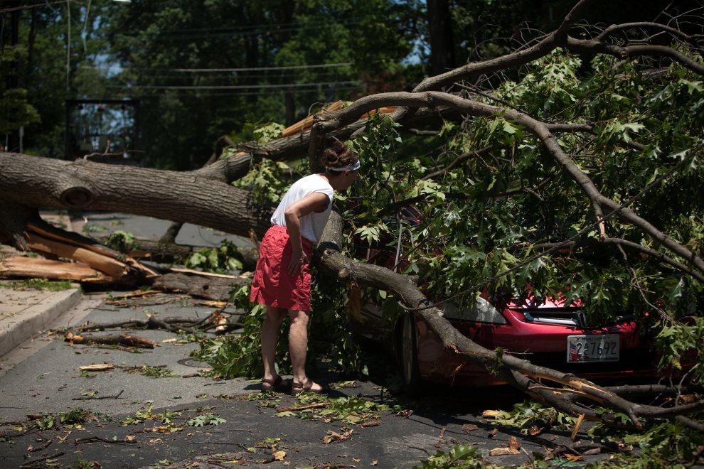 21.USA, Takoma Park, 30 czerwca 2012: Kobieta przygląda się samochodowi przygniecionemu podczas przez drzewo podczas burzy. Foto: Allison Shelley/Getty Images)