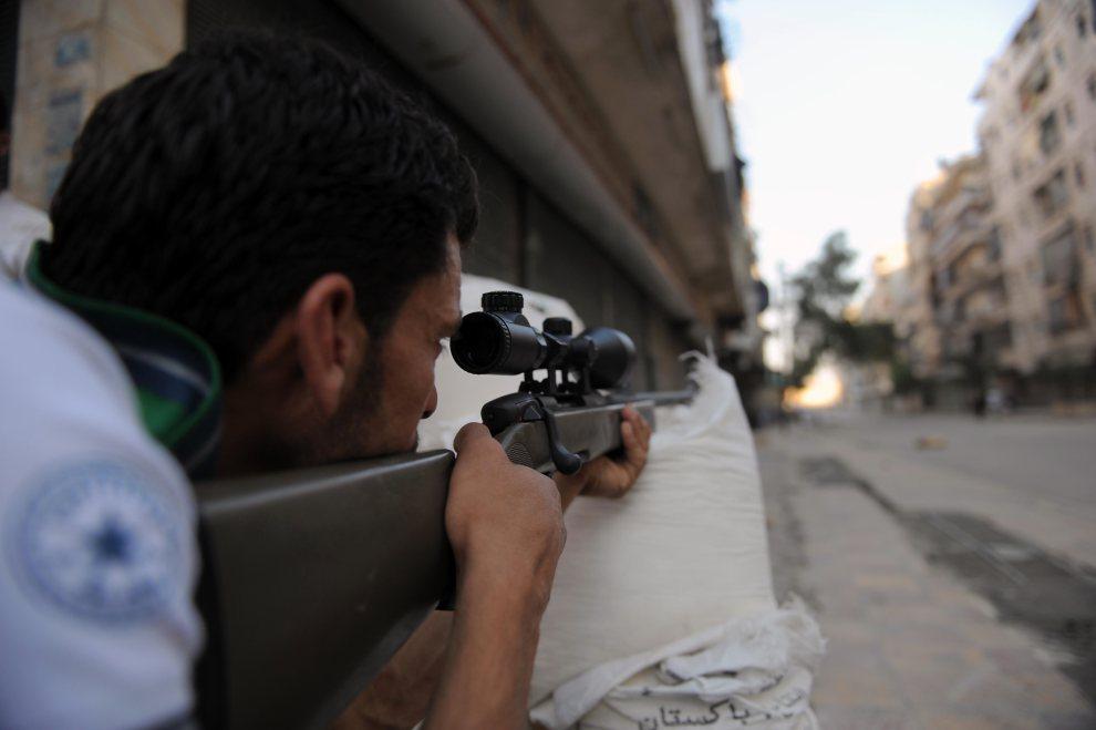 22.SYRIA, Aleppo, 25 lipca 2012: Rebeliant ostrzeliwuje ulicę w trakcie potyczki z siłami rządowymi. AFP PHOTO / BULENT KILIC