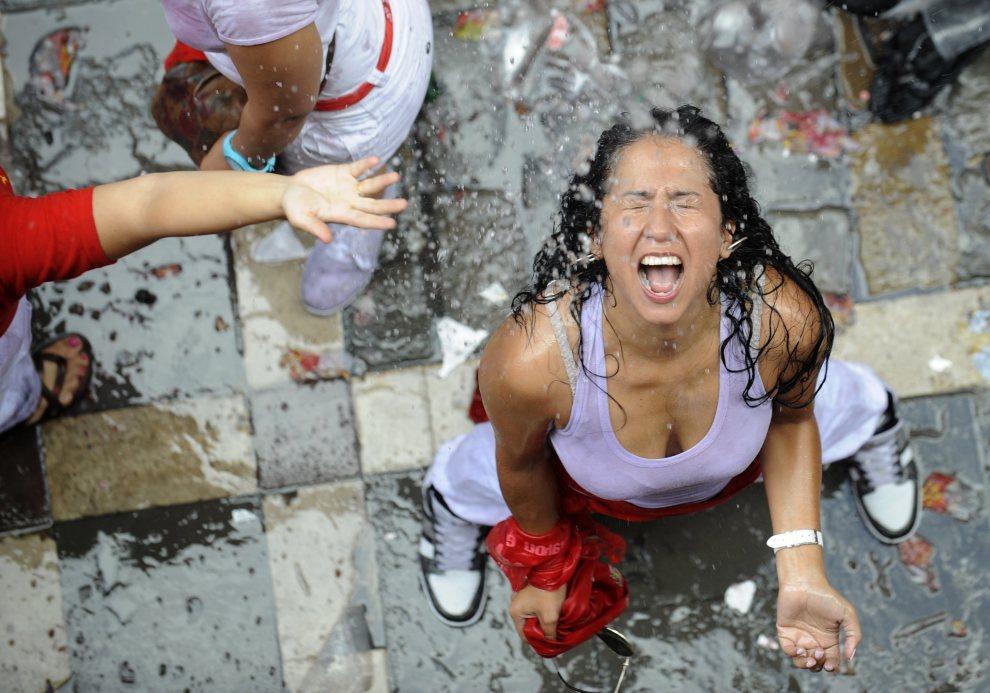 22.HISZPANIA, Pampeluna, 6 lipca 2012: Kobieta oblewana wodą przez pozostałych uczestników, stojących na balkonach. AFP PHOTO / Rafa Rivas
