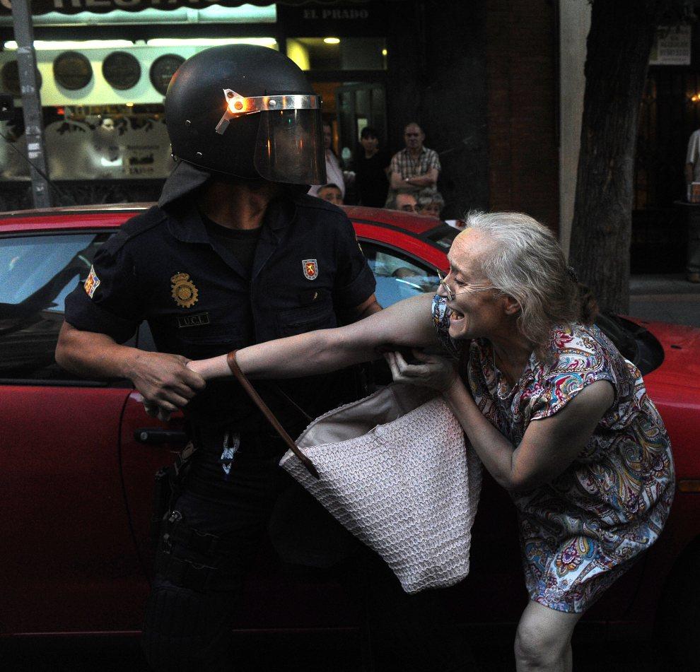 """25.HISZPANIA, Madryt, 13 lipca 2012: Policjant zatrzymuje kobietę w takcie protestów """"oburzonych"""". AFP PHOTO / DOMINIQUE FAGET"""