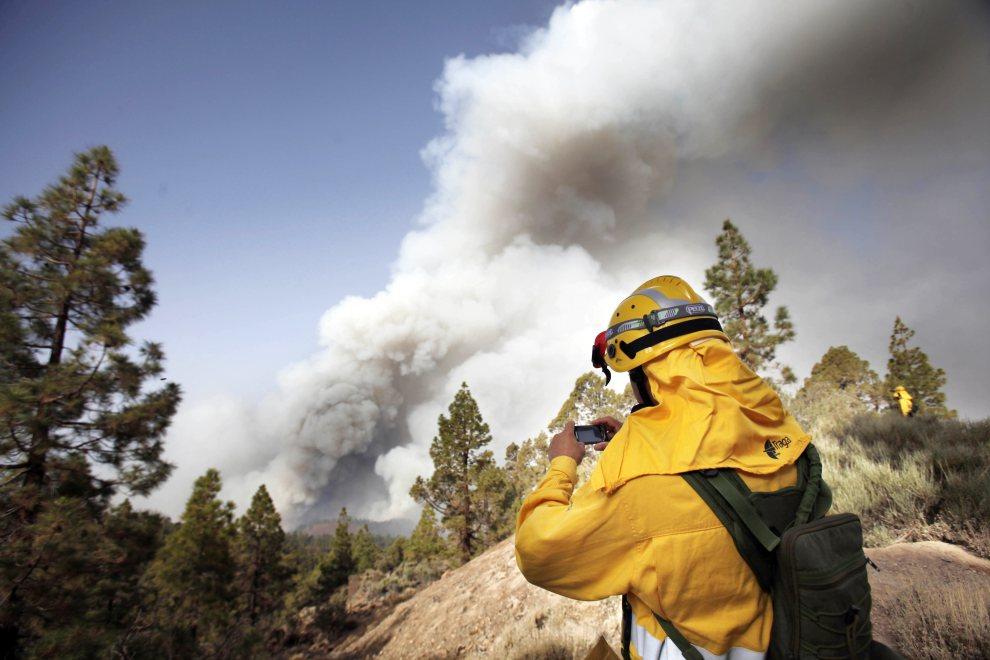 24.HISZPANIA, Teneryfa, 16 lipca 2012: Pracownik parku  z El Teine dokumentuje rozprzestrzenianie się ognia. AFP PHOTO / Desiree Martin