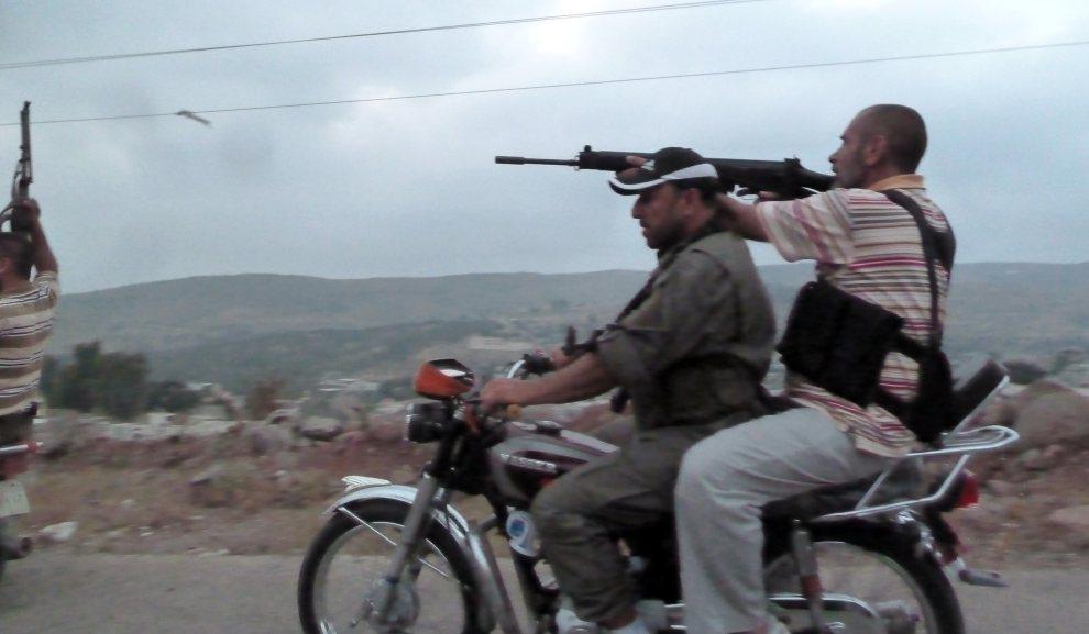 25.SYRIA, Azzara, 28 czerwca 2012: Rebelianci w pobliżu punktu kontrolnego na przedmieściach miasta Homs. AFP PHOTO/DJILALI BELAID