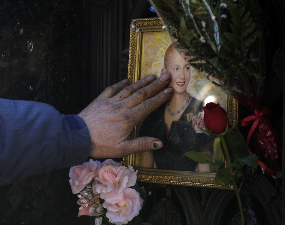 26.ARGENTYNA, Buenos Aires, 26 lipca 2012: Mężczyzna gładzi portret Evy Peron w 60. rocznicę jej śmierci. AFP PHOTO / Juan Mabromata