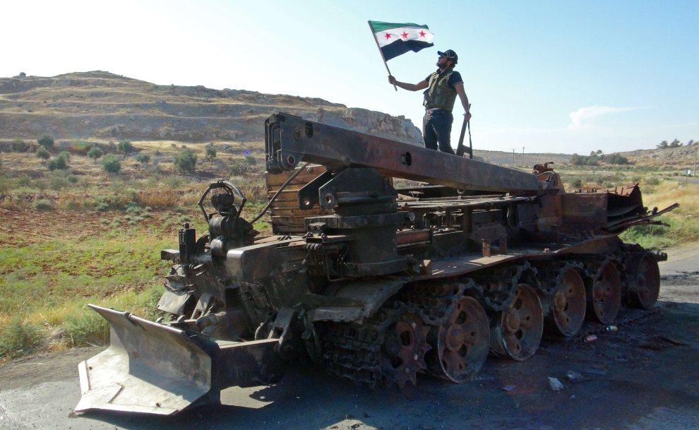 26.SYRIA, Binnisz, 14 lipca 2012: Rebeliant z flagą na zgliszczach pojazdu wojskowego. AFP PHOTO/HO/SHAAM NEWS NETWEORK