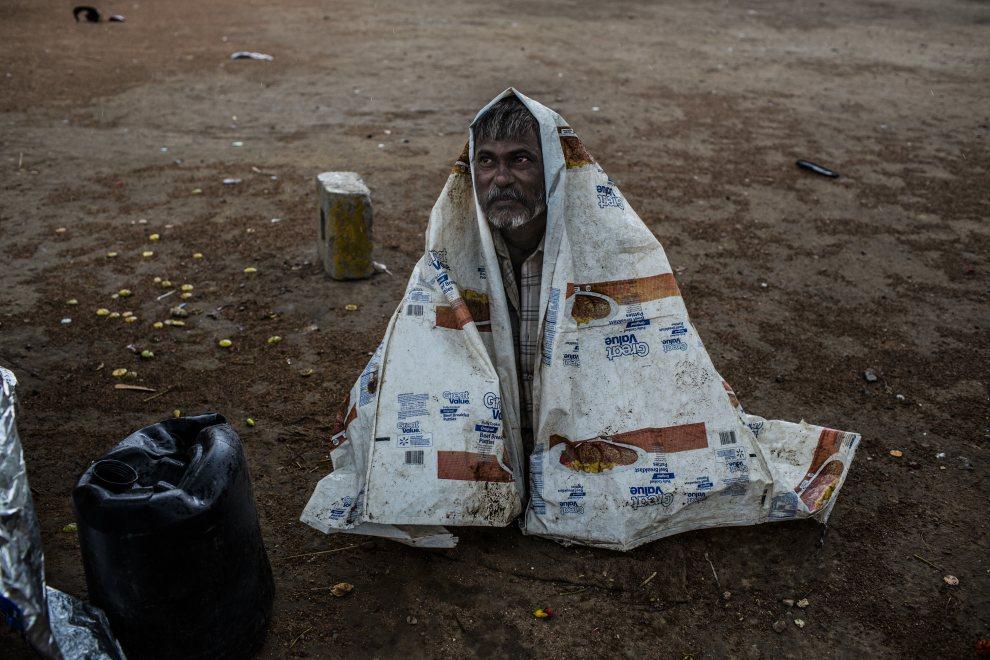 26.INDIE, New Delhi, 5 czerwca 2012: Mężczyzna nakryty folią chroni się przed deszczem. (Foto: Daniel Berehulak/Getty Images)