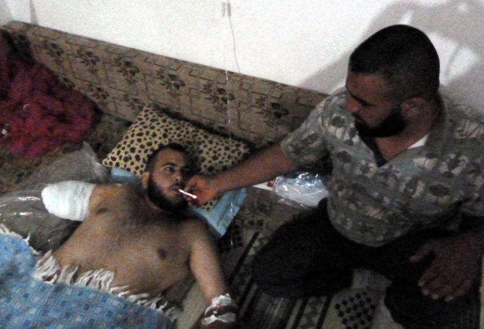 29.SYRIA, Azzara, 2 lipca 2012: Rebeliant podaje papierosa rannemu koledze. AFP PHOTO/DJILALI BELAID