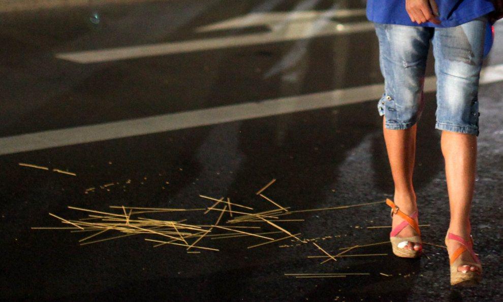 30.NIEMCY, Berlin, 28 czerwca 2012: Włoska kibicka mija rozrzucony na ulicy makaron. AFP PHOTO / ADAM BERRY