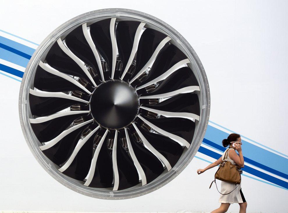 32.WIELKA BRYTANIA, Farnborough, 10 lipca 2012: Kobieta mija plakat reklamujący pokaz lotniczy. AFP PHOTO / ADRIAN DENNIS