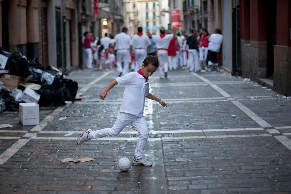35.HISZPANIA, Pampeluna, 8 lipca 2012: Chłopiec podążający za tłumem, bawi się piłką. (Foto: Pablo Blazquez Dominguez/Getty Images)